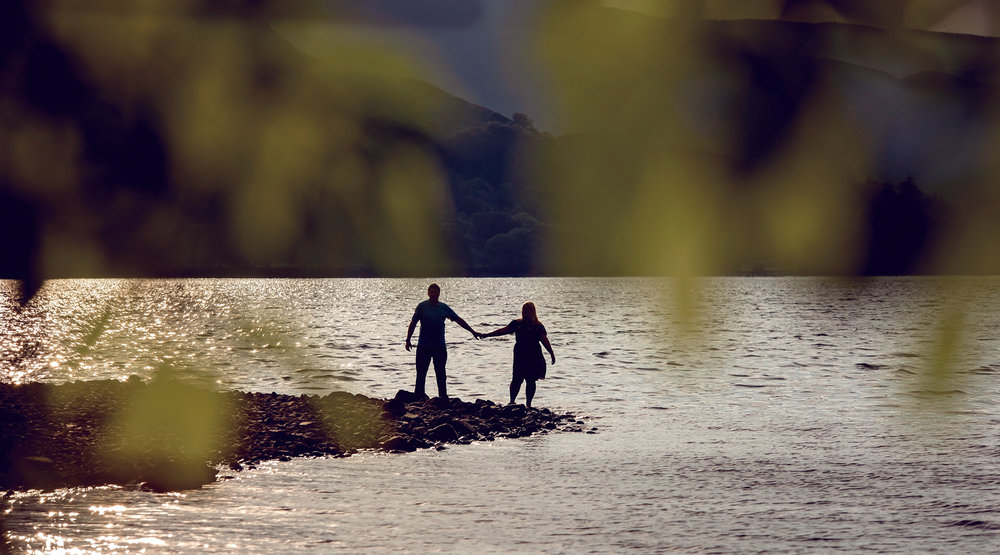 Pre shoot - A very distant and wide angle photo of a couple standing at the waters edge Derwent water in the Lake District