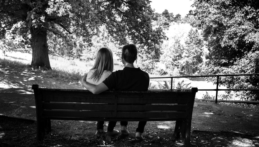 Pre shoot - A black and white photo of a couple sitting on a bench in a park in Manchester