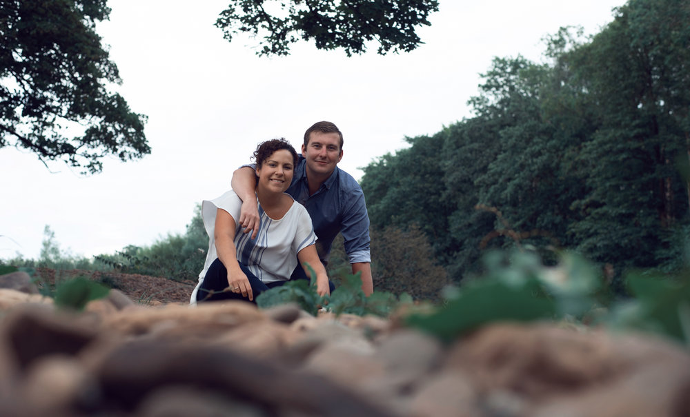 Pre shoot - portrait of a couple sitting on the stones by a river near Lanercost Priory Cumbria