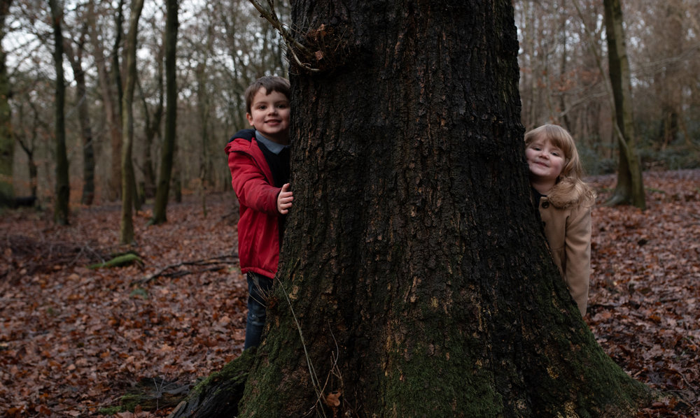 Two kids peeping around a tree in the woods