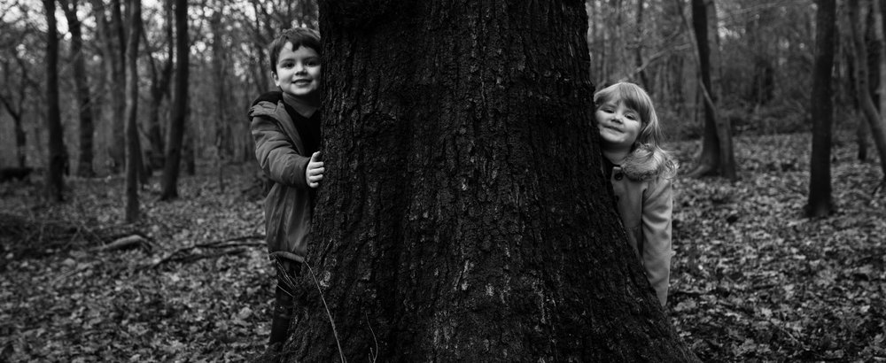 A black and white photograph of two kids peeping around a tree in the woods