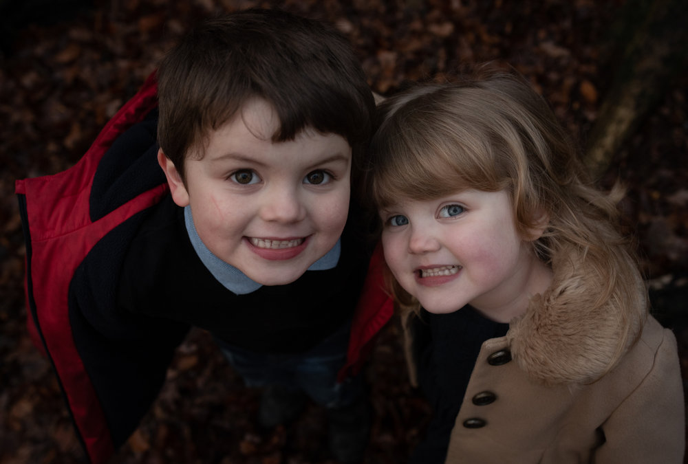 Two children looking up into the camera lens in the woods