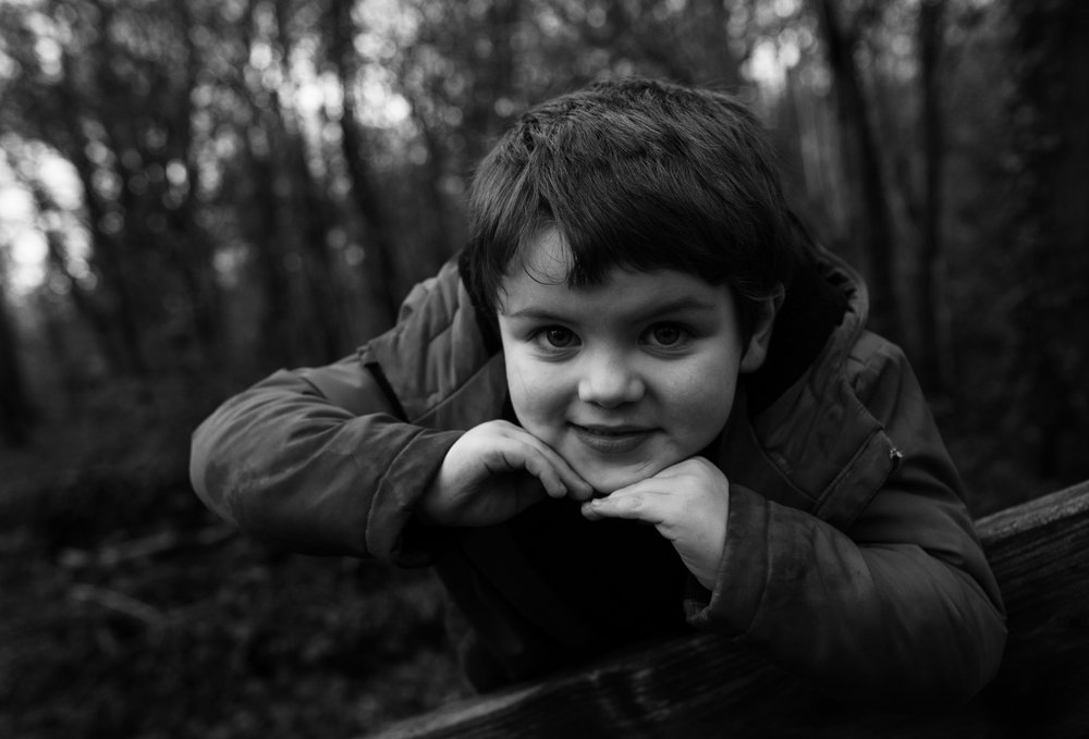 A black and white portrait of young lad in the woods
