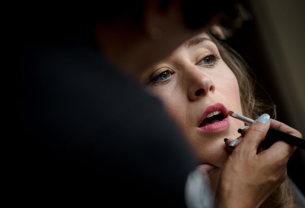 A bride having her lipstick applied by the makeup artist during morning bridal preparations