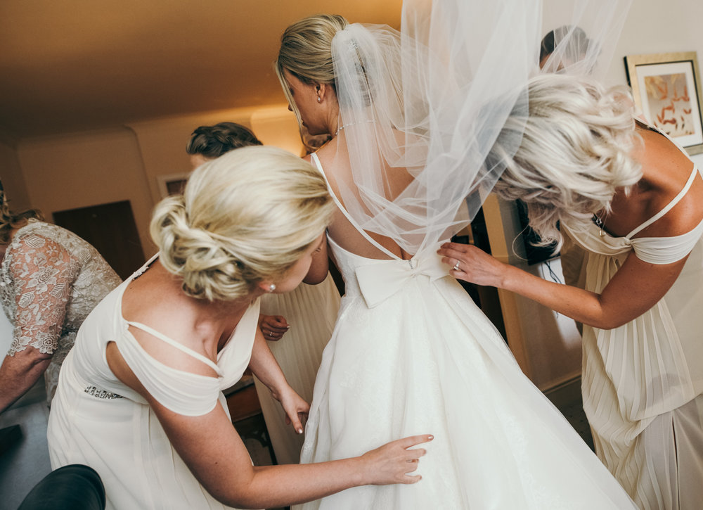 A bride being helped into her wedding dress during morning bridal preparations