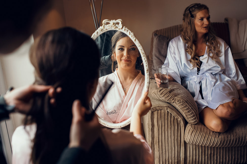 A bridesmaid having her hair styled during morning bridal preparations