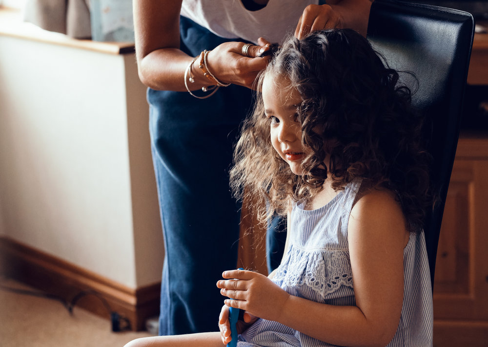 A little bridesmaid having her hair done during morning bridal preparations