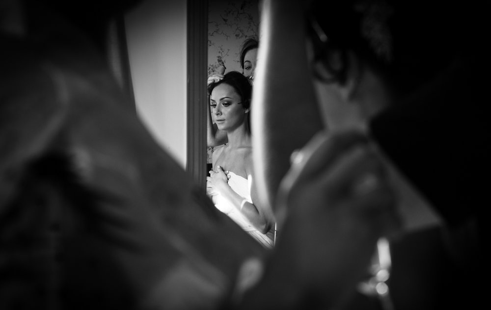 A black and white photograph of a bride getting into her dress during morning bridal preparations