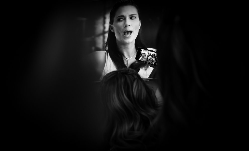 Crazy black and white photography of the bridesmaids taking a selfie during bridal preparations with a tv screen in the background