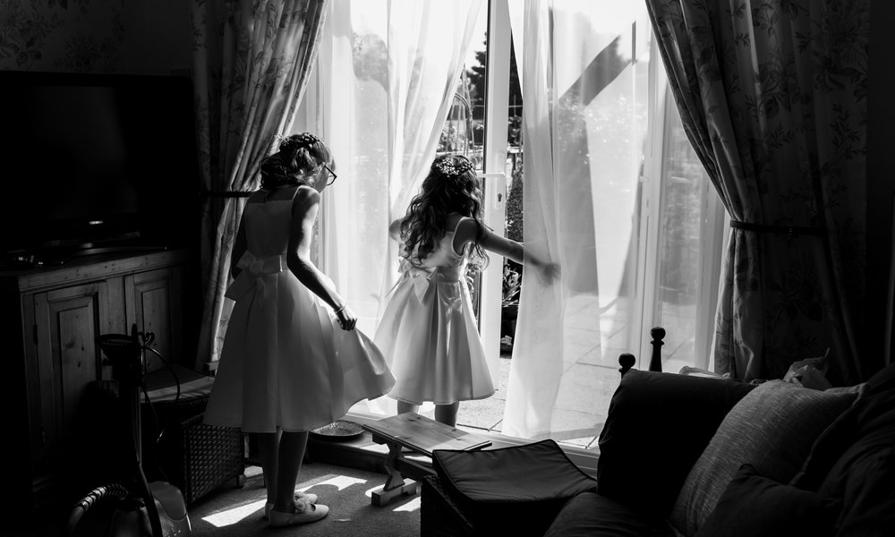 A black and white photograph of two young bridesmaids in their dresses playing about before leaving for the church