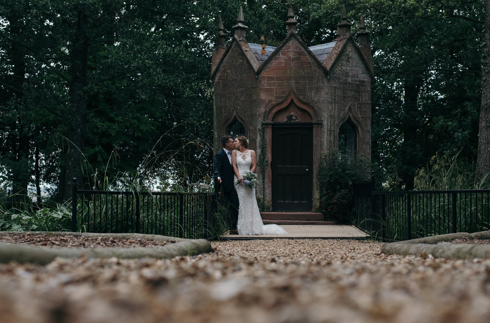 A bride and groom kissing near the old pumping station