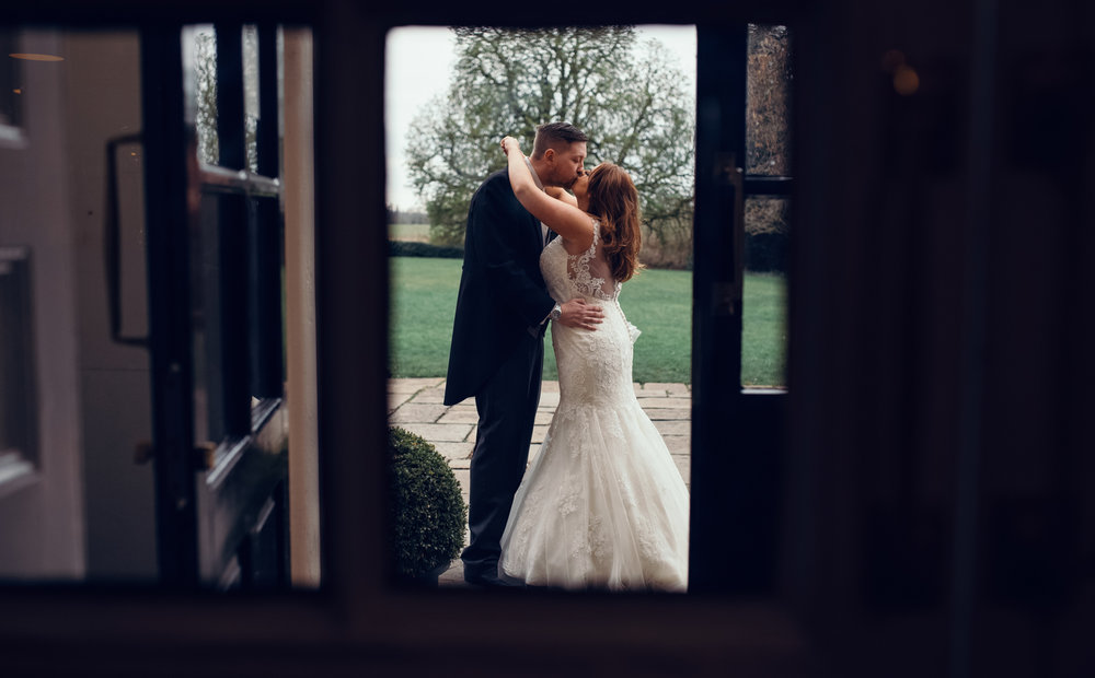 Bride and groom catching a sneaky kiss.jpg