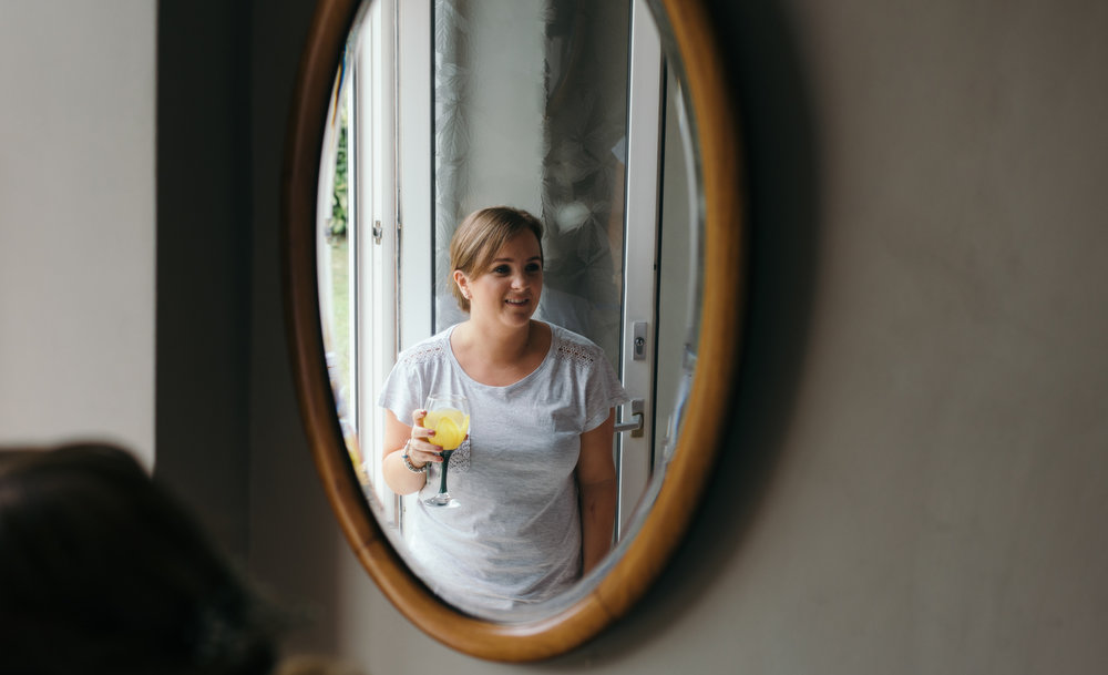 A bridesmaid enjoying a drink during preparations