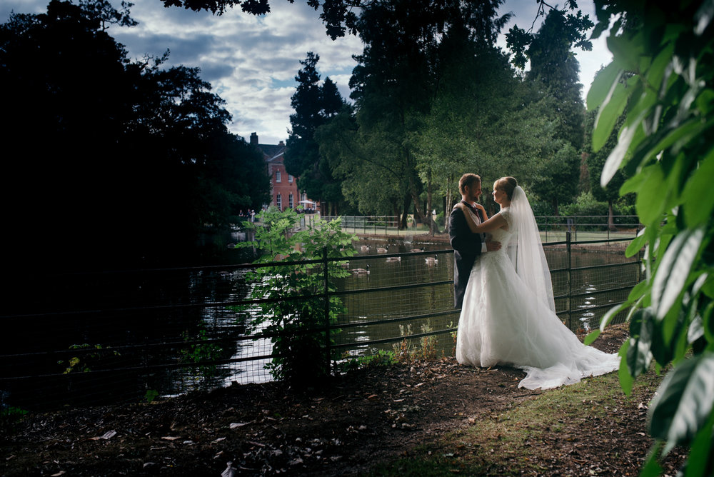 Romantic photo of the happy couple standing at the side of the lake at Motram Hall Hotel
