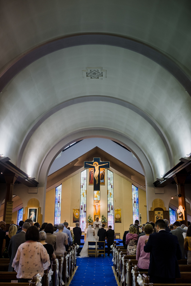 A photo taken from the very back of the church during the wedding ceremony