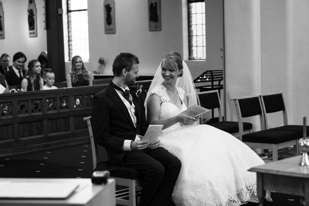 A black and white photo of the bride and groom chatting during the wedding ceremony