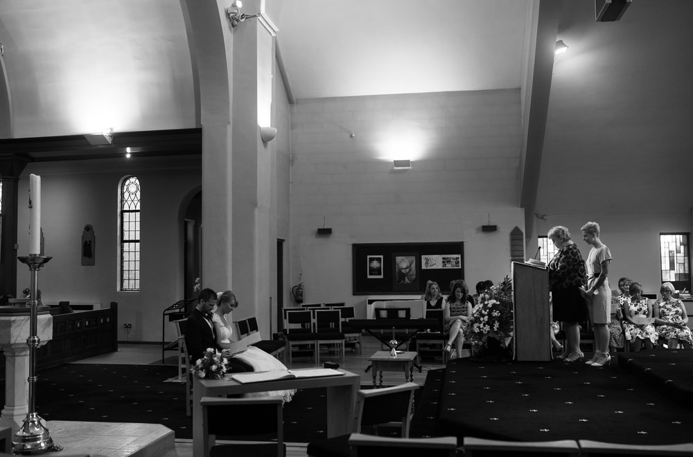 A black and white photo of the bride and groom sitting during the ceremony