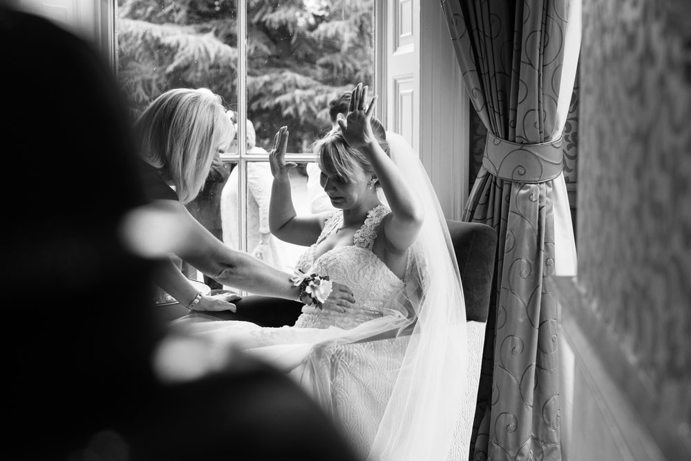 A black and white photo of the bride relaxing during the drinks reception