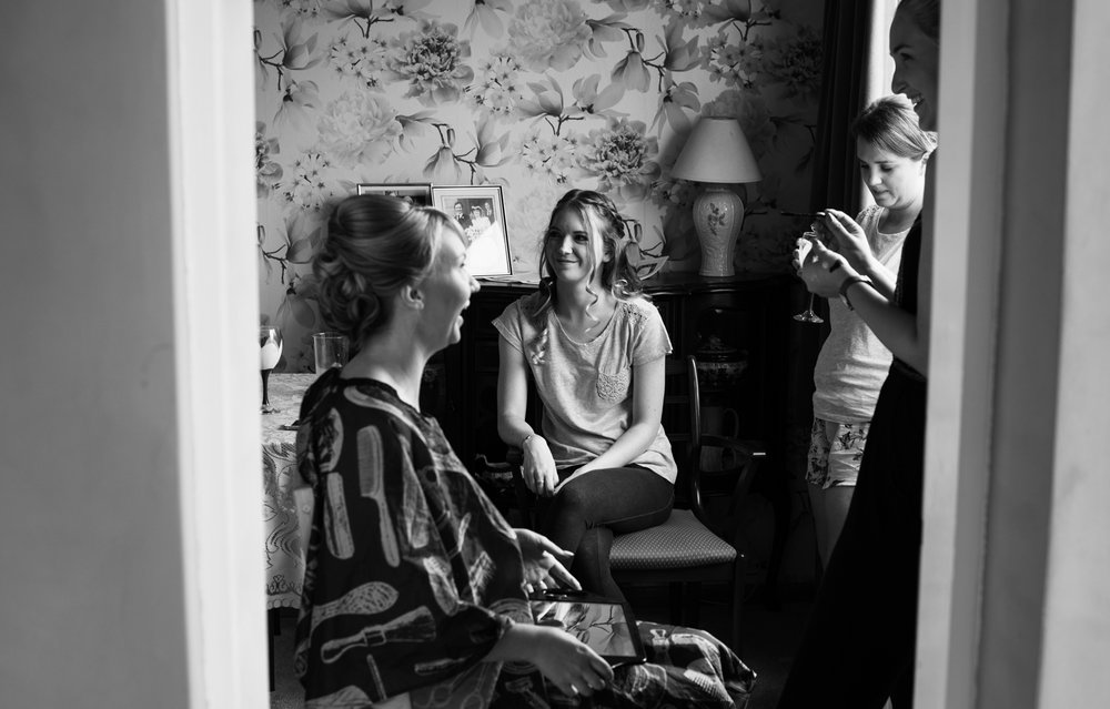 A black and white photo of the bride and bridesmaids during hair and makeup