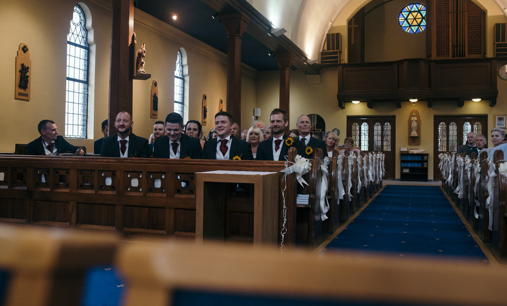 The groom best man and ushers sitting in the front rows of the church waiting for the bride and her father to arrive