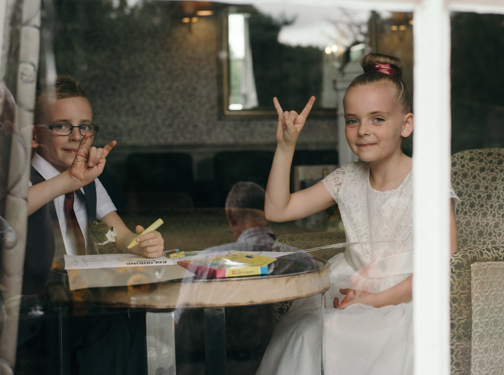 Tow young wedding guests doing the devils horns rock and roll sign through a window