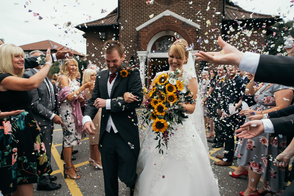 A bride and groom being showered in confetti