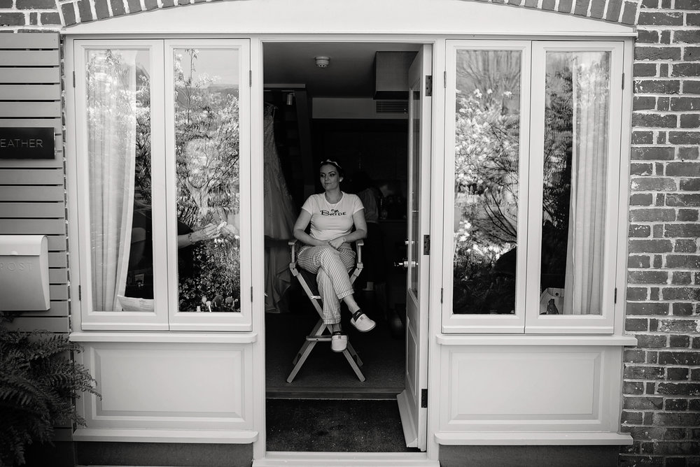 A black and white image of the bride sitting on a high chair having her makeup and hair done