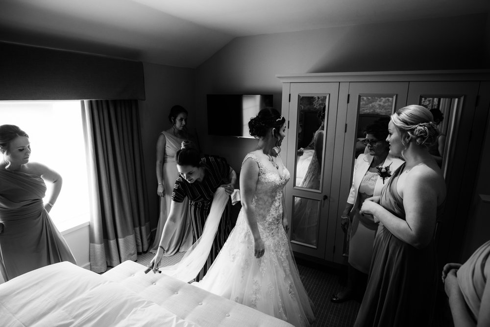 A black and white image of the bride surrounded by her bridesmaids and mother during bridal gown adjustments
