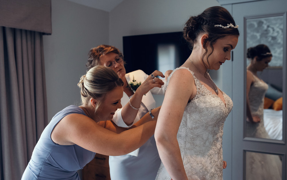 A bride bring helped into her wedding dress
