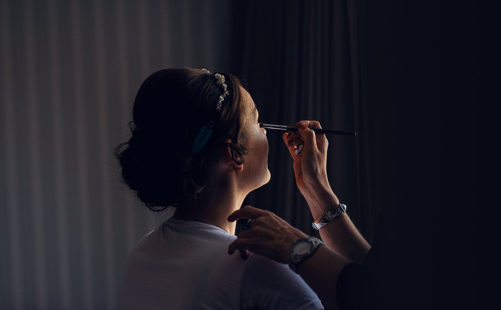 A bride having her makeup applied during morning preparations