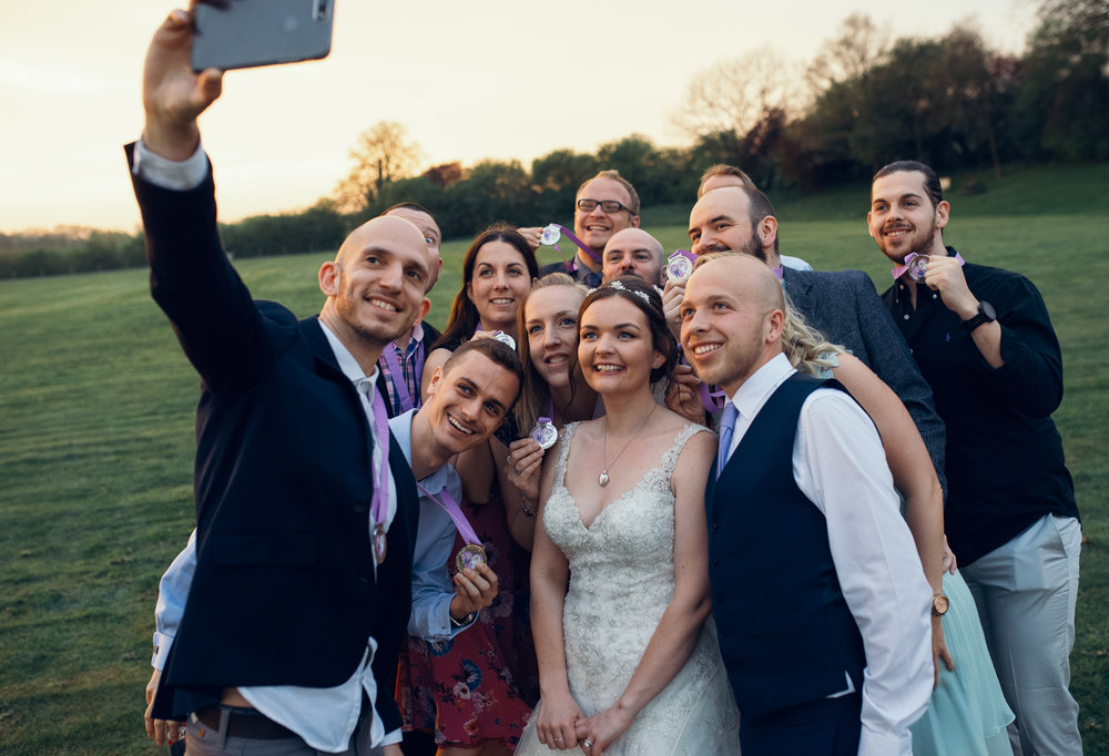 The bride and groom taking a selfie with all of their closest friends