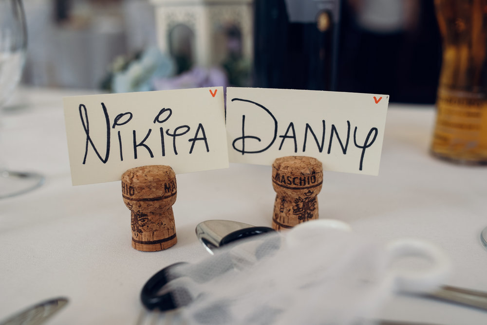 The bride and grooms names in corks used as place settings on the top table
