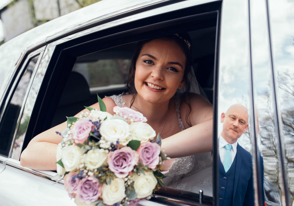 The bride sitting in the back of the car with her father reflected in a door panel