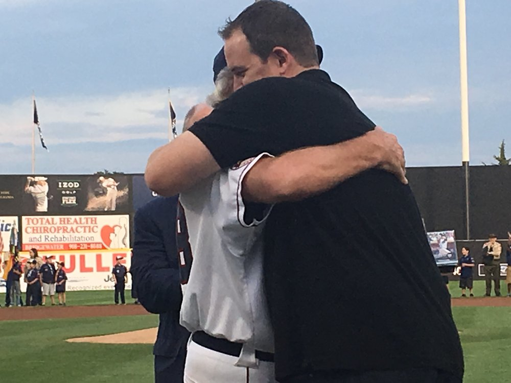 Patriot legend Josh Pressley hugs former coach Sparky Lyle