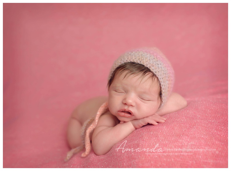 newborn posed in pink ruffles