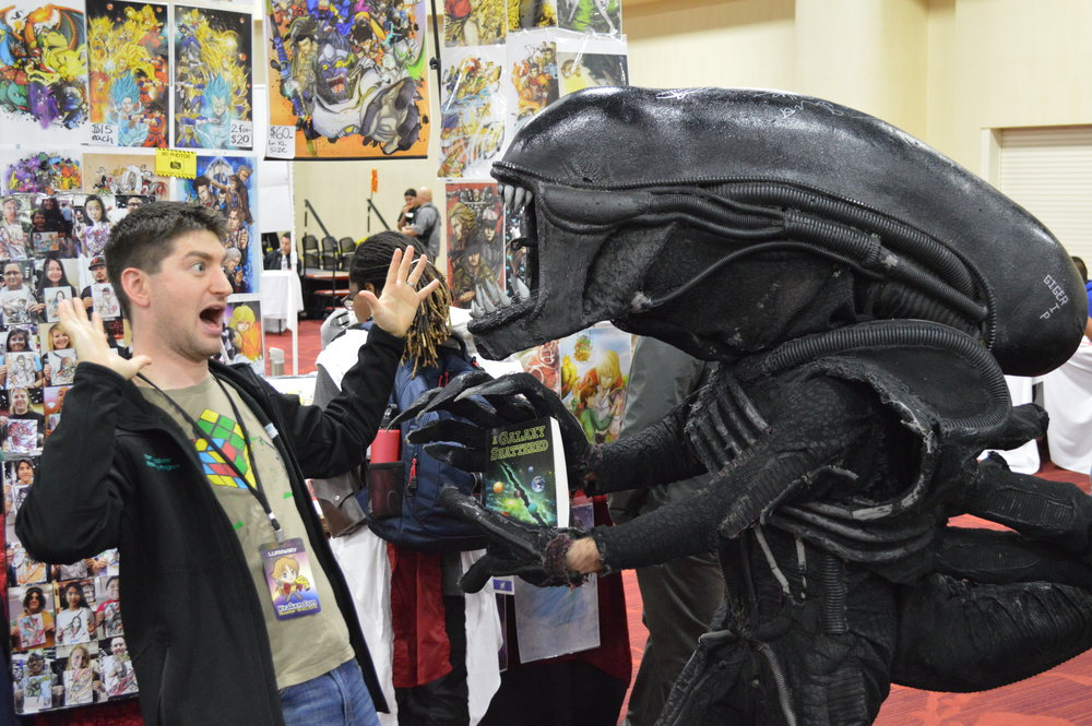 Me being attacked by a xenomorph over one of my books. It was not happy with my sales strategy.