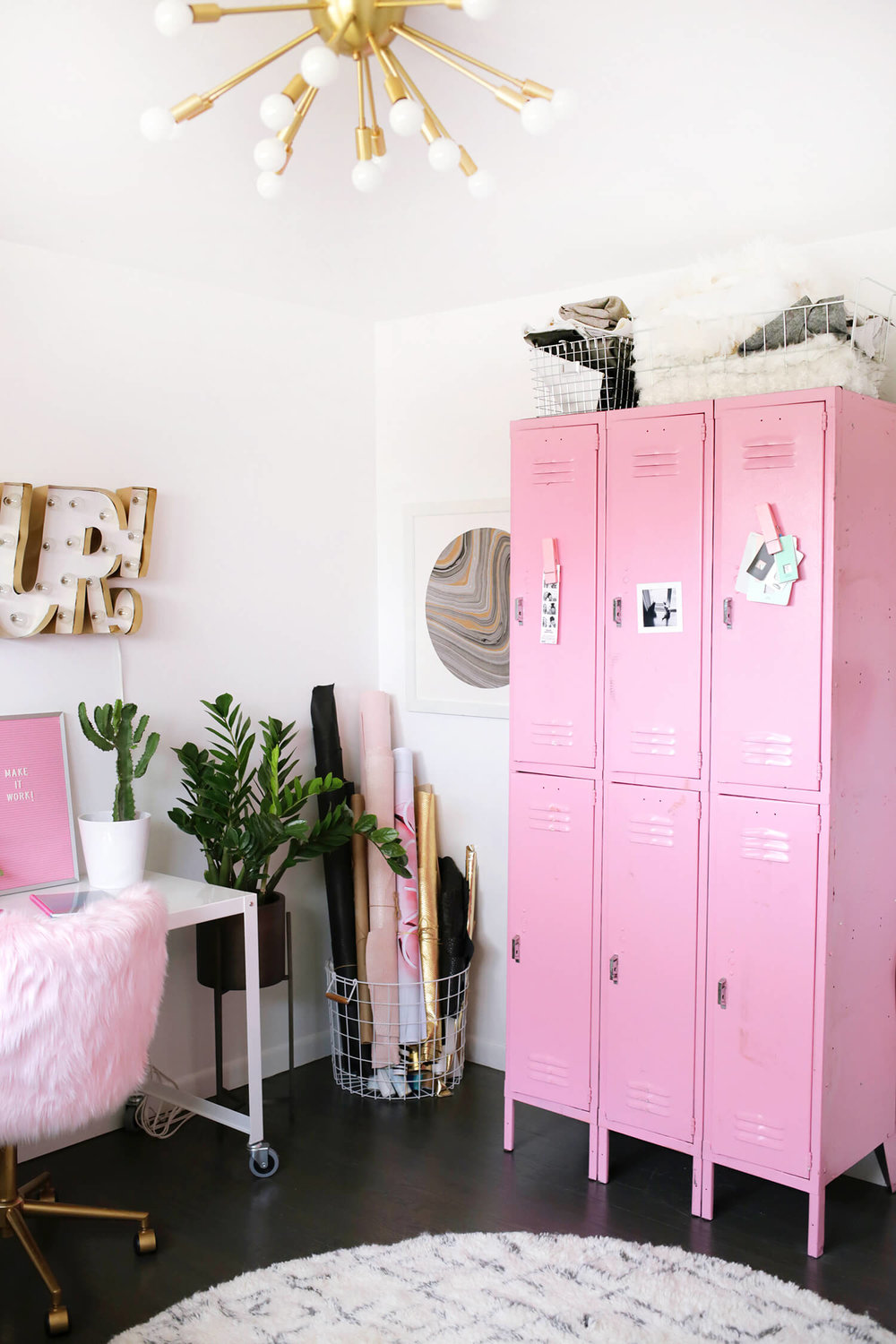 Laura's Craft Room from A Beautiful Mess  - closed storage is found in the pink lockers (swoon), while she displays rolls of fabric & vinyl in a basket.