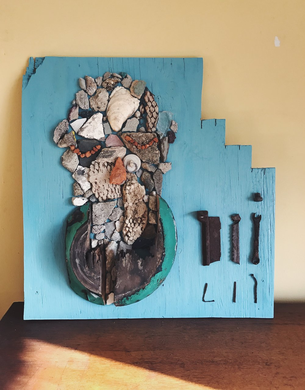 Found objects on wood: depicts the institutional negligence and gentrification experienced by the long-time residents of west Philadelphia's Mantua neighborhood in 2016; made of objects and debris found on the streets of Mantua.
