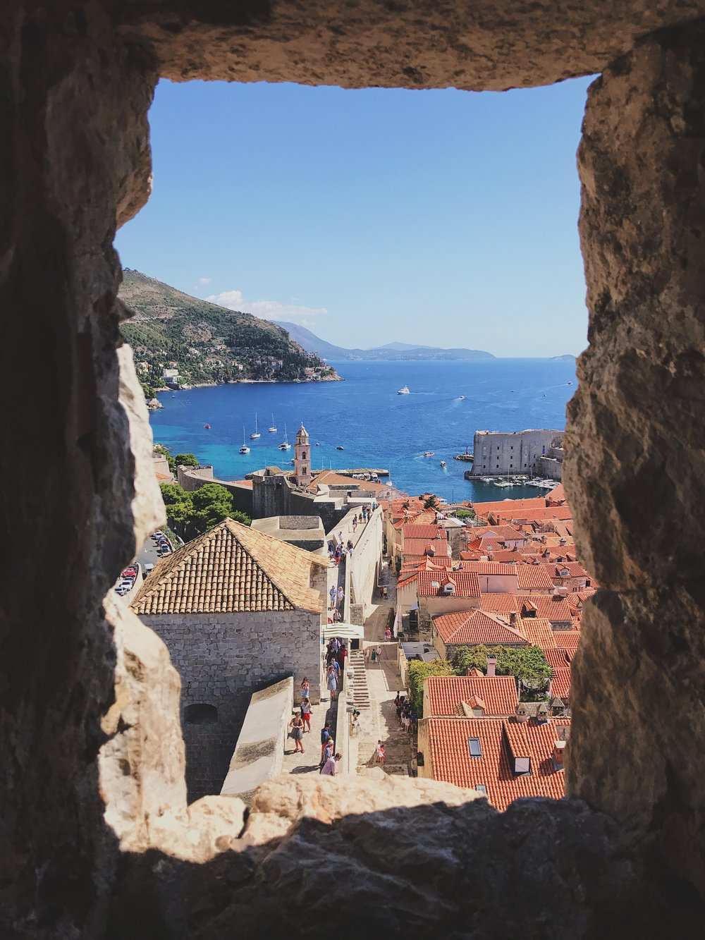 A view of old town and the Adriatic sea through a window in the wall