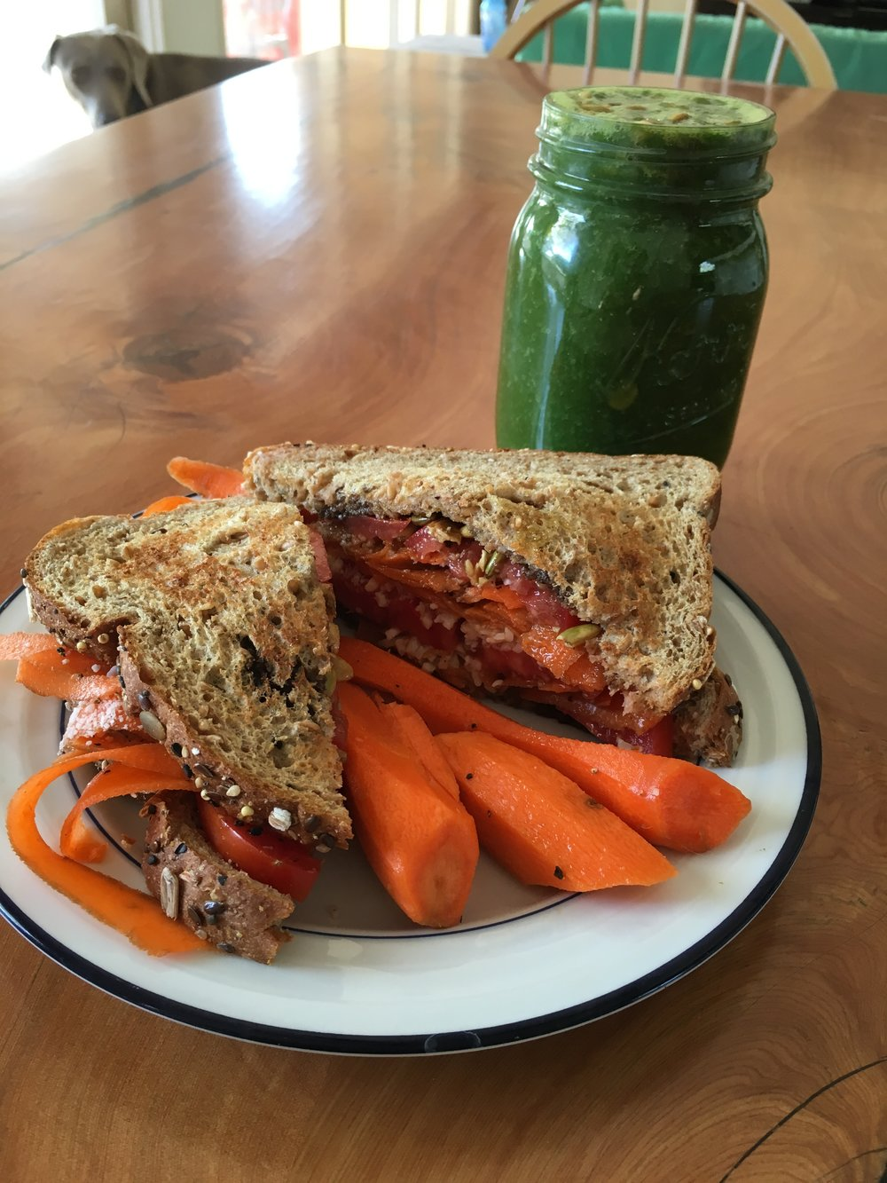 """Veggie sandwich and """"Everyday"""" green juice: Shaved carrots, tomatoes, shredded almond cheese, pepitas on Dave's Power Seed bread. In the green juice: Two apples, one banana, water, two handfuls of kale, juice of one lemon, Moon Juice adaptogens, chia seeds, curry powder, and pepitas."""