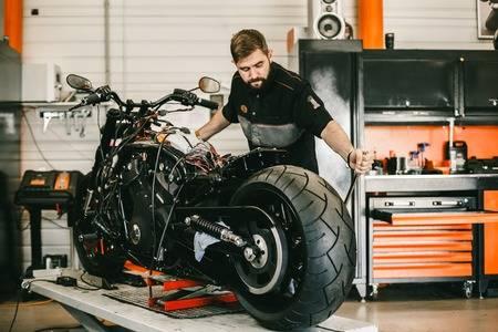 81125289-mechanician-changing-motorcycle-wheel-in-bike-repair-shop-professional-motorcycle-mechanic-working-i.jpg