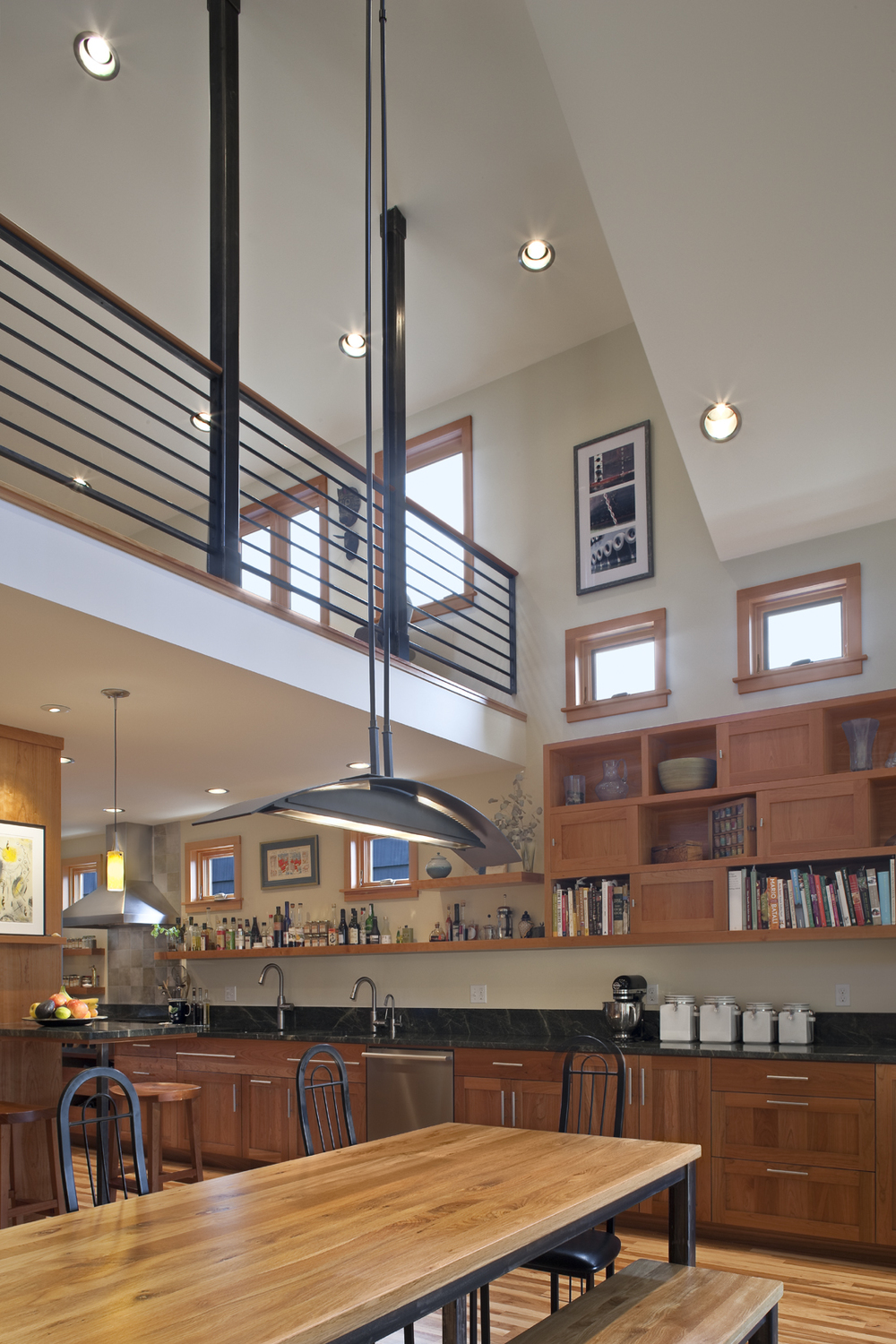 Double height dining room addition to Seattle home showing custom metal guardrail at the catwalk above the Dining Room with cherry Kitchen cabinets and open shelving beyond