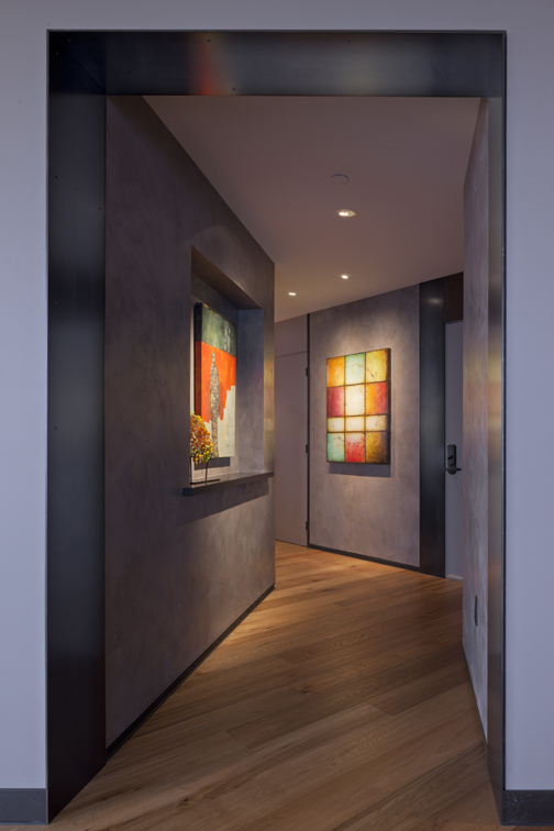 Hallway design in seattle condo showing metal base, new door hardware, plaster walls, great art and recessed art lighting