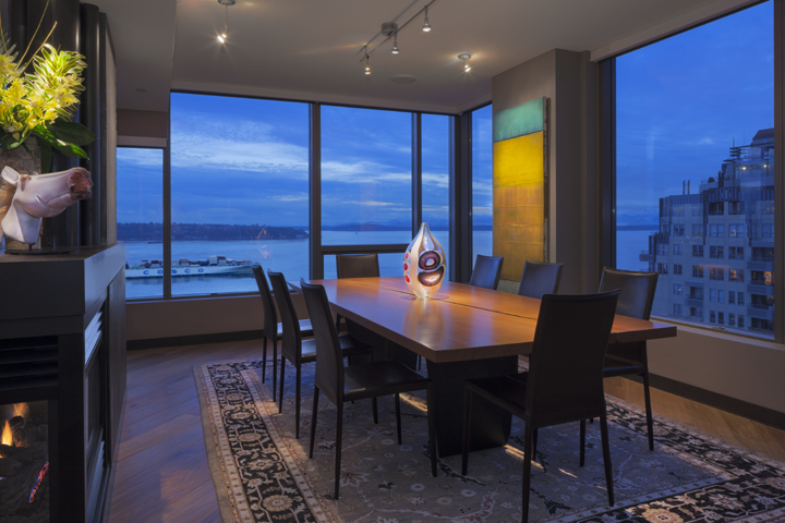 contemporary seattle architectural condo design with reclaimed wood dining table, beautiful art and great view