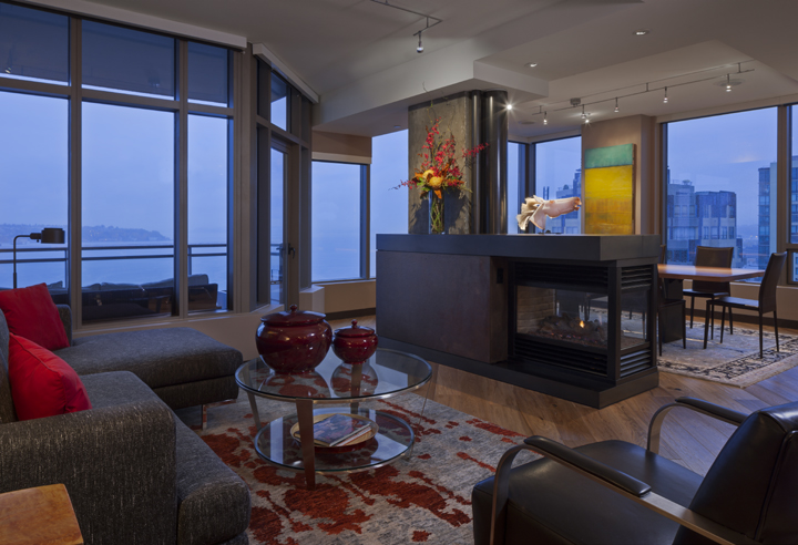 modern Seattle living room design with metal surround over gas fireplace, hardwood floors and track lighting