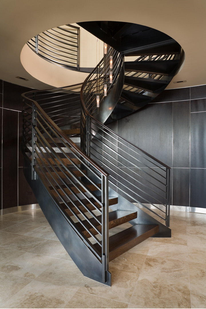 Curved Seattle spiral staircase, travertine floors and curved wood wall with hidden doors beyond