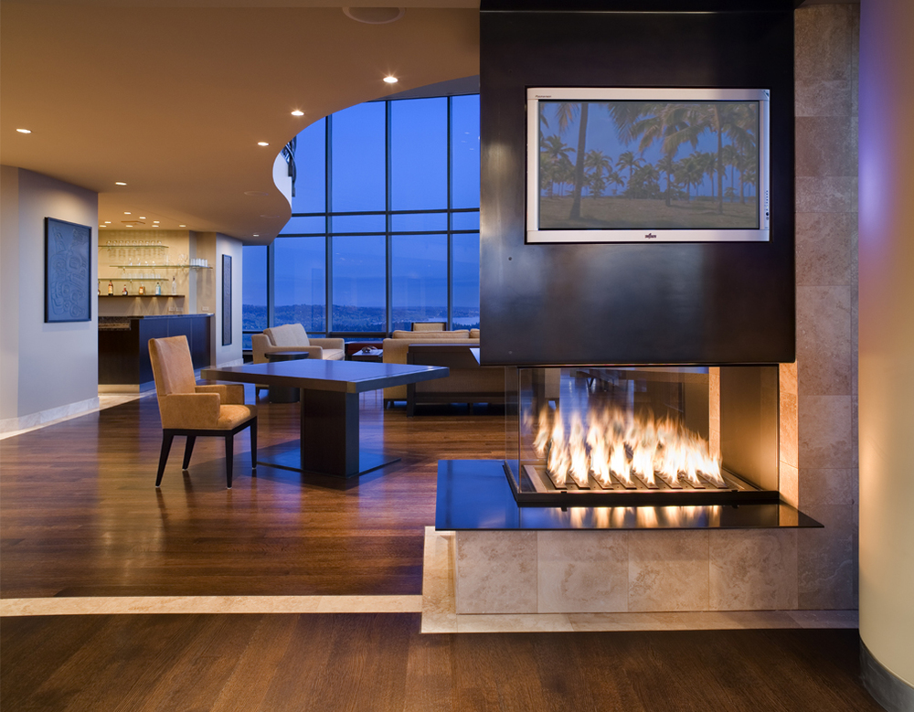 Seattle condo design showing custom steel and wood gas fireplace surround, hardwood floors, and great living room beyond