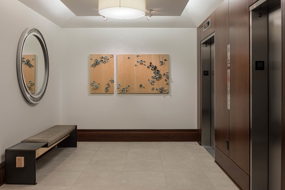 condo lobby showing bright white tile floor, up-lighting, a maple, steel and leather bench, oval steel and porcelain mosaic mirror and wood wall panels