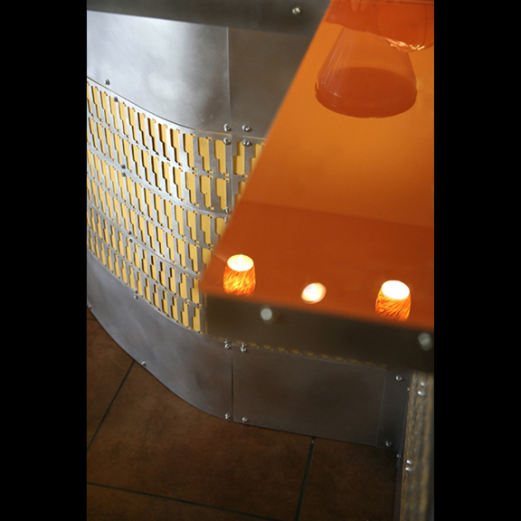 Coffee shop counter with orange back-painted glass and steel cabinet inlay