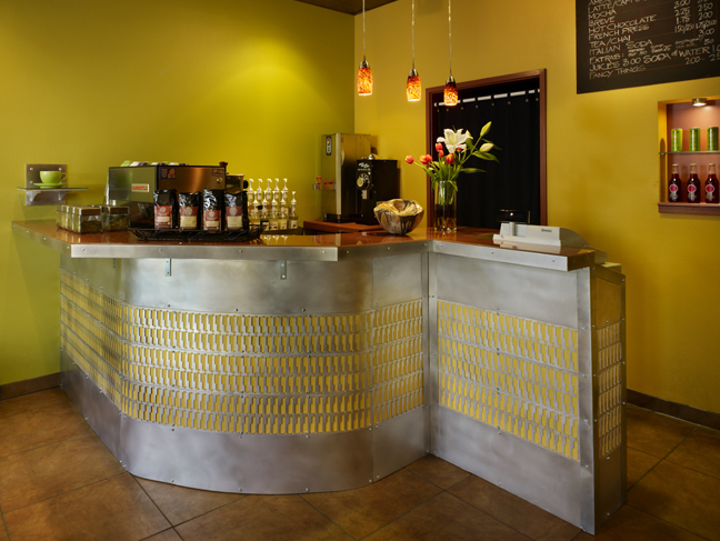 Coffee counter in cafe with steel inlay, back-painted glass tops, a product niche beyond showing colorful bottles and cans, a handmade bowl, a vase of flowers and pendant lighting